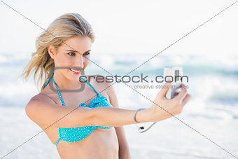 Cheerful sexy blonde in bikini taking a self picture