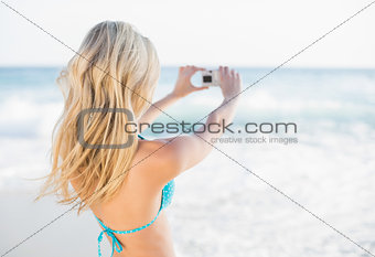 Rear view of attractive blonde in bikini taking a self picture