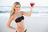 Happy sexy blonde in elegant bikini holding cocktail