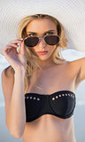 Gorgeous blonde in elegant black bikini looking over her sunglasses