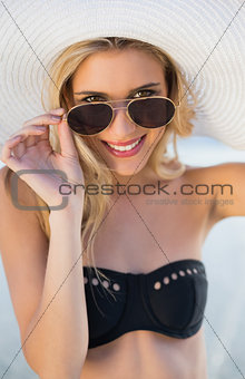Smiling blonde in elegant black bikini looking over her sunglasses