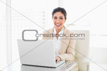 Happy businesswoman working on a laptop