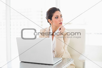 Thoughtful businesswoman working with a laptop