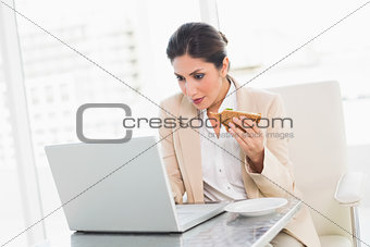 Focused businesswoman eating lunch as she is working