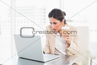 Concentrating businesswoman drinking coffee while working on laptop