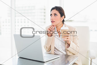 Thoughtful businesswoman drinking coffee while working on laptop