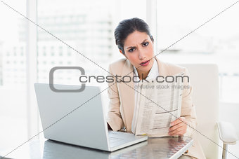 Stern businesswoman holding newspaper while working on laptop looking at camera