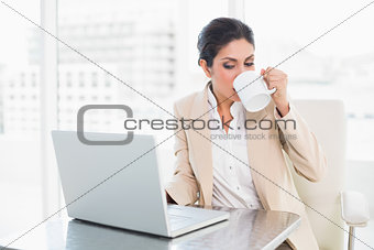 Cheerful businesswoman drinking from mug while working on laptop