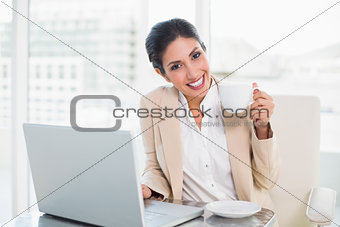 Happy businesswoman holding cup while working on laptop