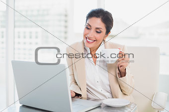 Happy businesswoman holding cup while typing on laptop