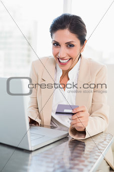 Happy businesswoman shopping online with laptop