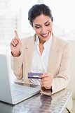 Happy businesswoman shopping online with laptop and pointing