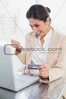 Excited businesswoman shopping online with laptop
