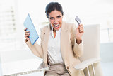 Cheering businesswoman shopping online with tablet pc