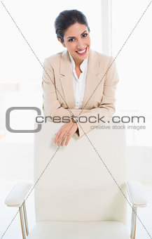 Stylish businesswoman standing behind her chair