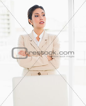 Stern businesswoman standing behind her chair