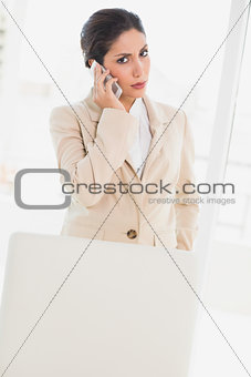 Frowning businesswoman standing behind her chair on the phone looking at camera