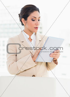 Businesswoman standing behind her chair using digital tablet