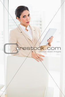 Frowning businesswoman standing behind her chair holding tablet pc