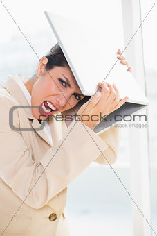 Crazed businesswoman hitting head off laptop looking at camera