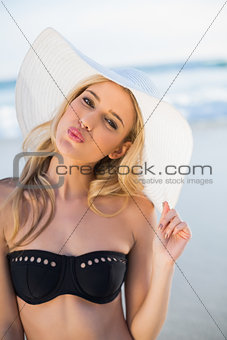 Pretty sensual blonde in elegant black bikini wearing straw hat