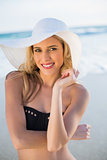 Cheerful sensual blonde in elegant black bikini wearing straw hat