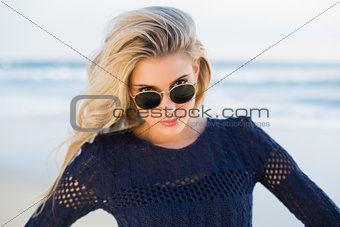 Cheerful sensual blonde looking over her sunglasses