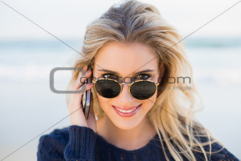 Cheerful gorgeous blonde on the phone looking over her sunglasses