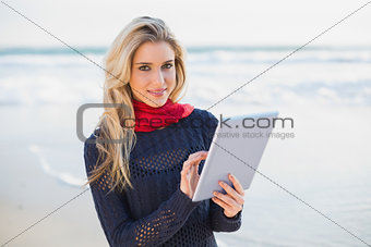 Cheerful sexy blonde holding tablet computer
