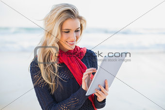 Smiling sexy blonde using tablet computer