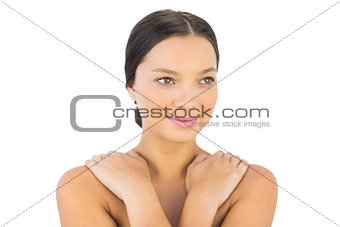 Cheerful woman crossing arms over shoulders