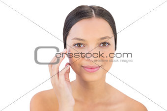 Smiling woman spreading beauty cream on her cheek