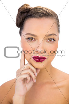 Attractive woman with red lips touching her cheek