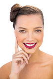 Pretty woman with red lips touching her cheek smiling at camera