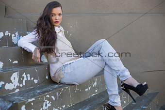 Attractive woman with red lips sitting on stairs posing