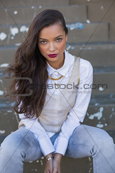 Trendy woman with red lips sitting on stairs