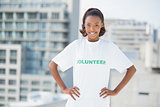 Smiling woman with hands on hips wearing volunteer tshirt