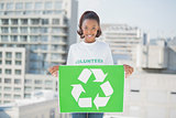 Cheerful woman holding recycling sign
