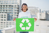 Serious volunteer woman holding recycling sign