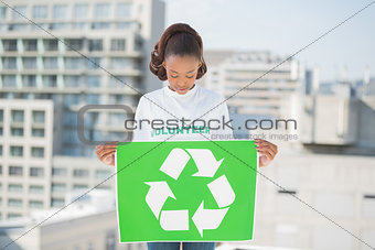 Pretty volunteer woman holding recycling sign