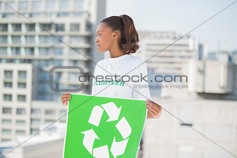 Cute volunteer woman holding recycling sign looking away