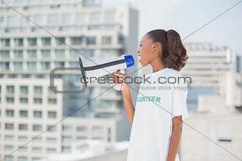 Cute volunteer woman shouting in megaphone