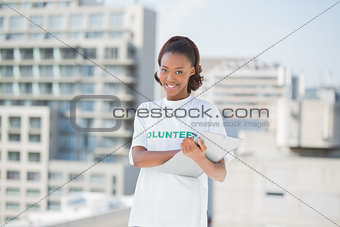 Smiling volunteer woman holding clipboard