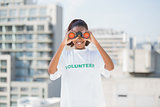 Smiling woman with volunteer tshirt using binoculars