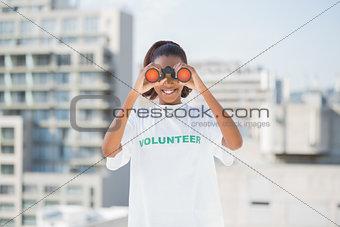 Smiling woman with volunteer tshirt using binoculars