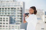 Woman with binoculars looking at camera