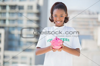 Happy volunteer holding piggy bank