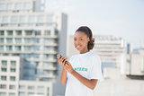 Cheerful volunteer holding her mobile phone