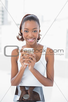 Happy sporty model holding coffee