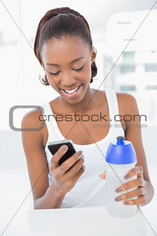 Smiling athletic woman looking at her smartphone